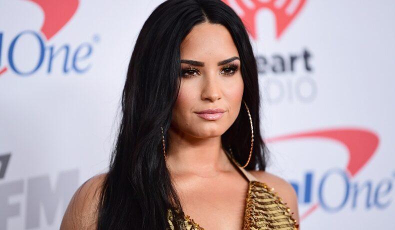 Demi Lovato, pe covorul roșu la Jingle Ball în 2018. Fundal alb, ea e îmbrăcată în rochie aurie, cu părul lung și negru cercei mari