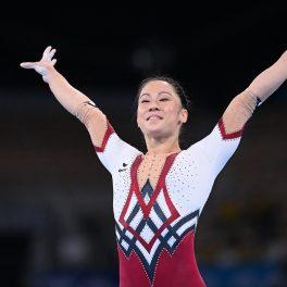Kim Bui în timp ce poartă un costum dintr-o singură piesă cu mâneci albe și pantaloni roși și zâmbește în fața juraților de la Jocurile Olimpice de la Tokyo 2020