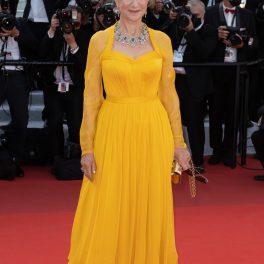 Helen Mirren pe covorul roșu la Festivalul de Film de la Cannes în timp ce poartă o ținută monocormatică, într-o rochie coplet galbenă