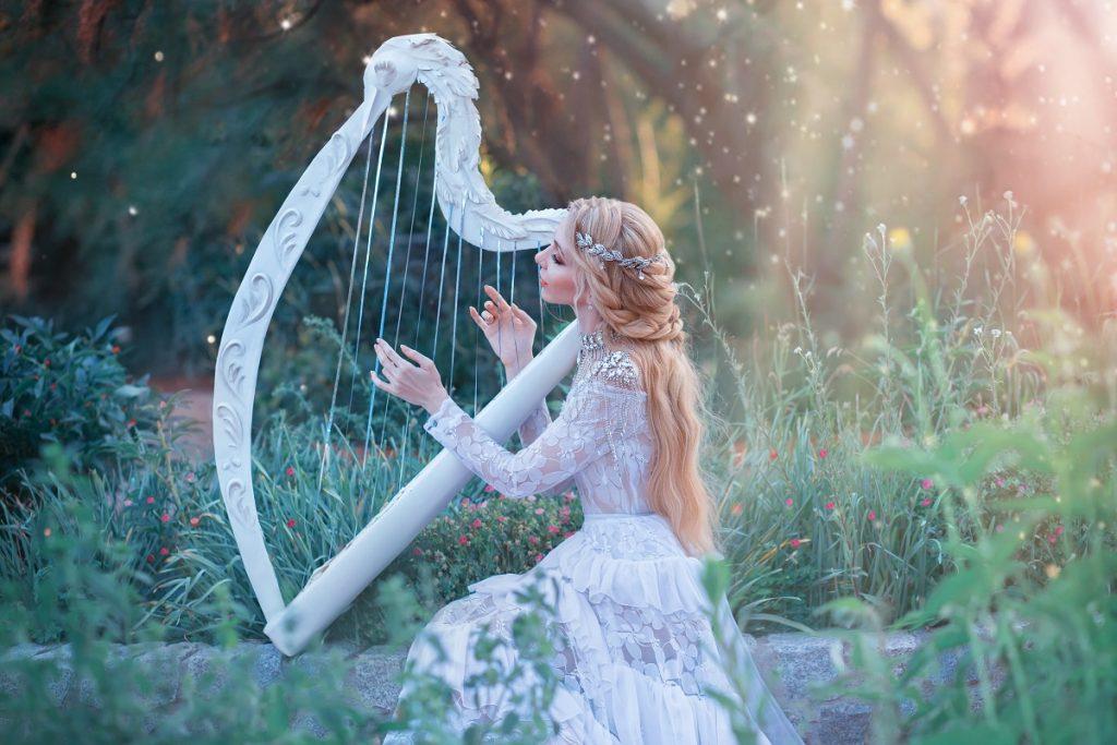 O femeie frumoasă care se află într-o pădure în timp ce cântă la o harpă albă pentru a sugera o tehnică din horoscopul seducției