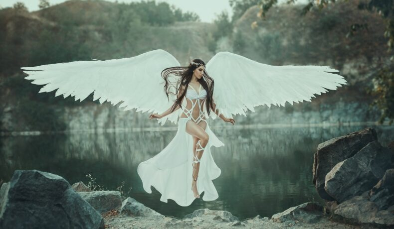 O femeie frumoasă care levitează în fața unui lac și poartă un costum alb și aripi de înger pentru a demonstra cum să pui în practică horoscopul seducției