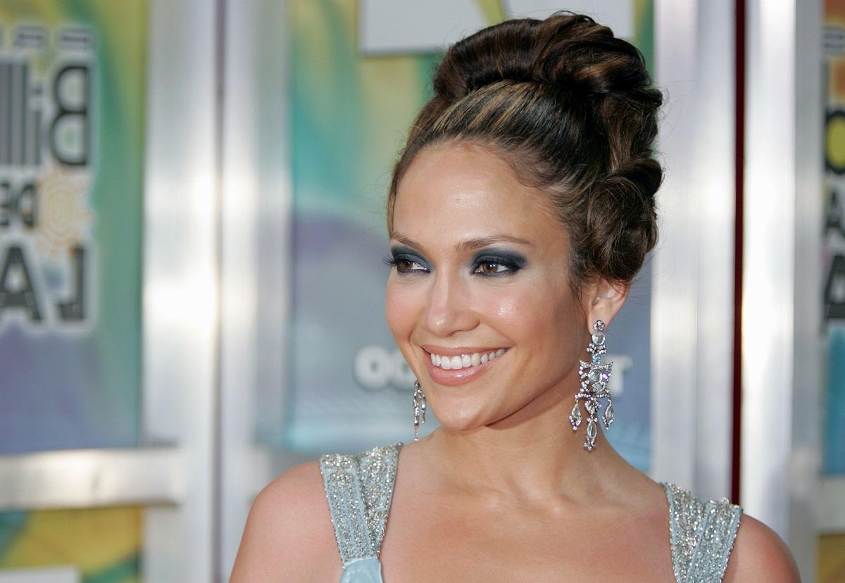 Portret al cântăreței Jennifer Lopez care poartă părul într-un coc și zâmbește la cameră la Billboard Latin Music Awards din 2005