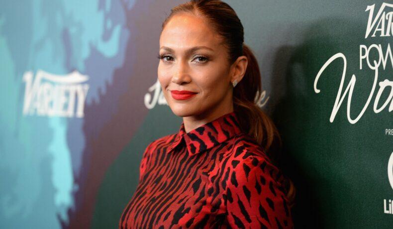 Jennifer Lopez pe covorul roșu purtând o rochie roșie cu pete negre la Variety Power of Women în 2014