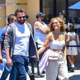 Jennifer Lopez într-o ținută de stradă în timp ce îl ține de mână pe iubitul său Ben Affleck și îi zâmbește larg în parcul de distracții Universa Studios