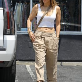 Jennifer Lopez într-un crop-top alb și o pereche de pantaloni cre în timp ce așteaptă în parcare