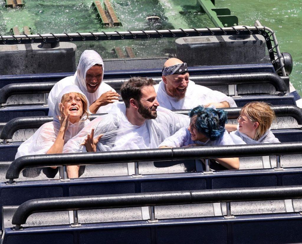 Jennifer Lopez purtând o pelerină de ploaie alături de Ben Affleck și gemenii săi în timp ce se dau într-un carusel pe apă în cadrul parcului de la Universal Studios din Hollywood