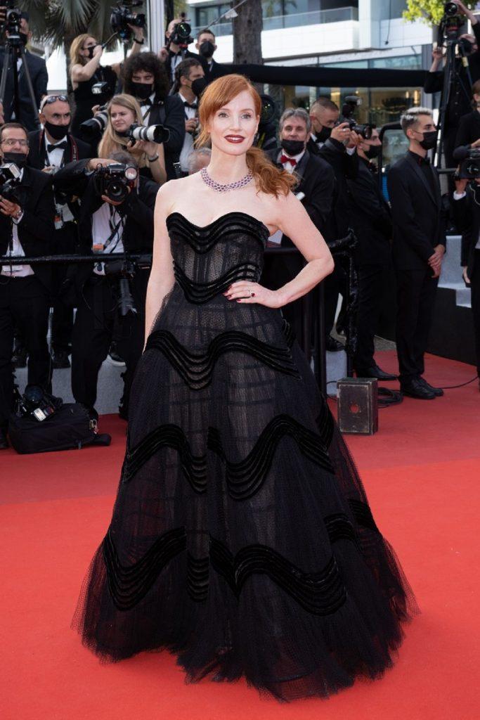 Jessica Chastain pozând cu o mână în șold în timp ce zâmbește la cameră și poartă o rochie de prințesă neagră pe covorul roșu