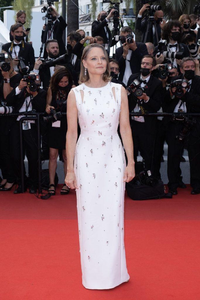 Jodie Foster pe covorul roșu la festivalul de film de la Cannes, purtând o rochie mulată pe corp, albă cu paiete gri