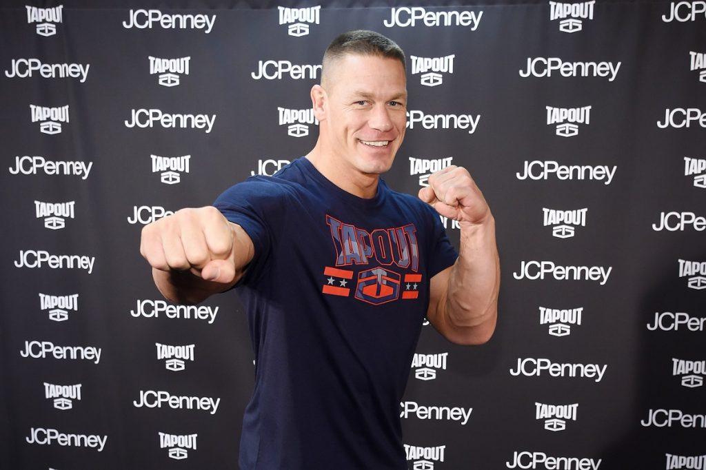 John Cena într-un tricou gri în timp ce își ține brațele încordate și arată cu pumnul către public la o conferință de fitness din New Tork din 2017