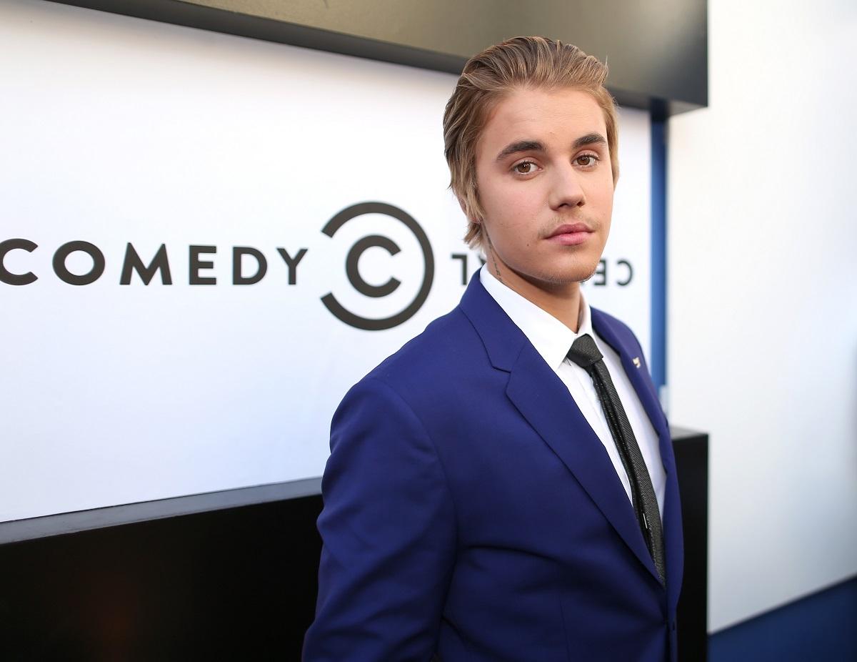 Justin Bieber într-un costum albastru cu cravată în timp ce se află pe covorul roșu la The Comedy Central Roast în anul 2014