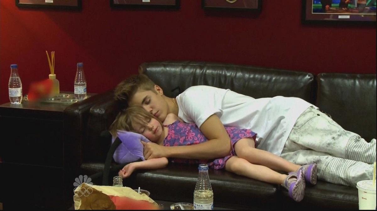 Justin Bieber într-un costum alb de scenă în timp ce doarme pe o canapea și o ține în brațe pe sora lui mai mică în timpul turneului All Around The World