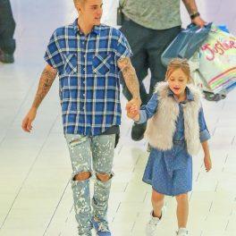 Justin Bieber într-o ținută casual cu blugi rupți și o cămașă albastră în carouri în timp ce o ține pe sora lui, Jazmyn de mână la cumpărături în mall