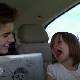 Justin Bieber într-o mașină ținând un laptp în mână în timp ce zâmbește alături de sora lui mai mică, Jazmyn în timpul turneului All Around The World