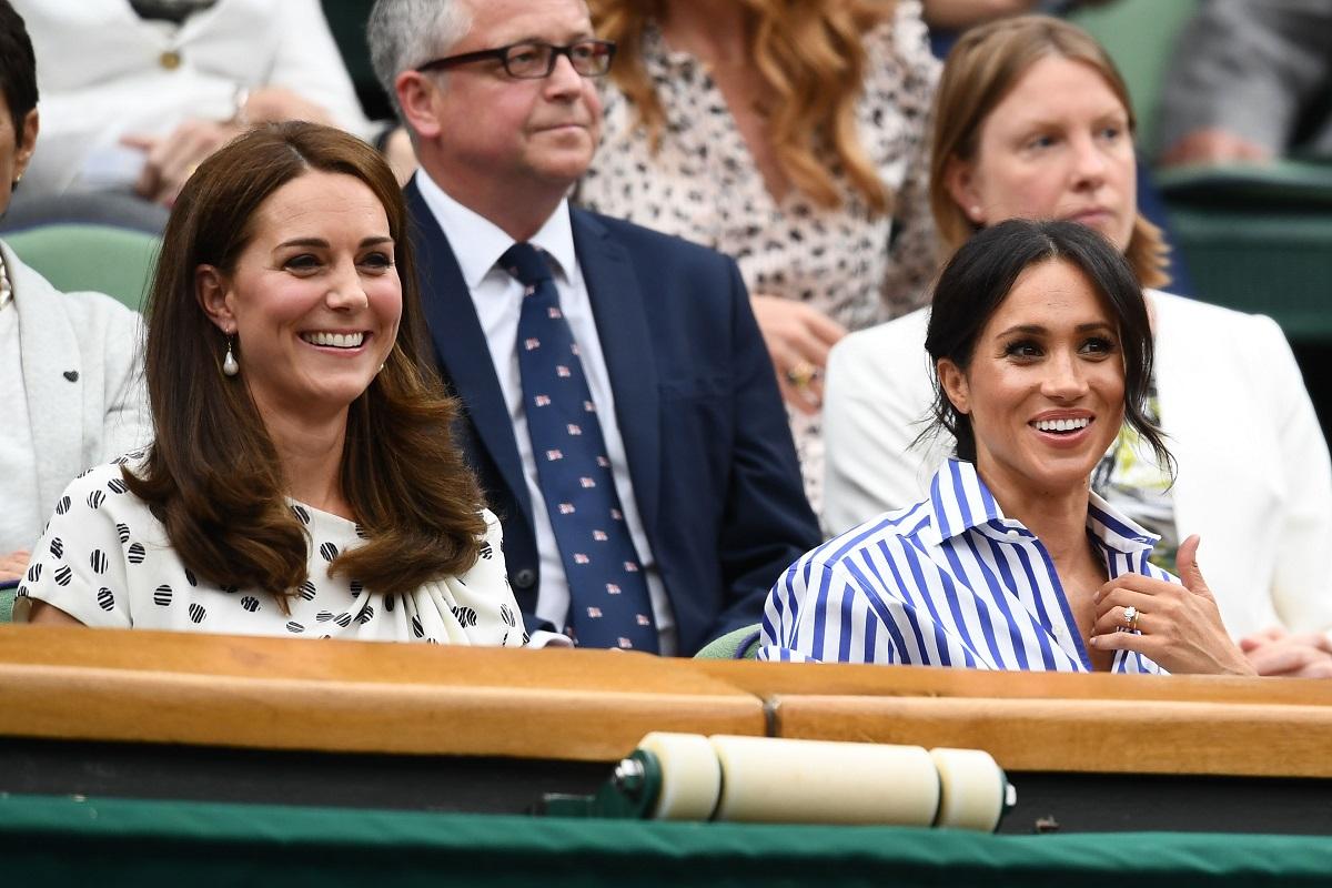 Kate Middleton în timp ce zâmbește în tribuna de la Wimbledon 2018 alături de Ducesa de Sussex, Meghan Markle