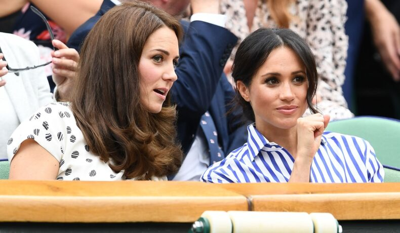 Kate Middleton și Meghan Markle la Turneul Wimbledon în iulie 2018. Cele două au fost surprinsă în timp ce râdeau și glumeau. Kate purta o bluză albă cu buline negre și Meghan purta bluza albă cu dungi albastre