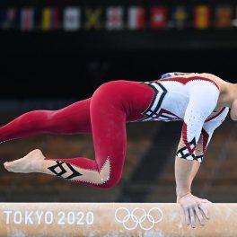 Gimnasta Kim Bui în timp ce execută un exercițiu la bârnă și stă sprijinită doar în mâini în cadrul Jocurilor Olimpice de la Tokyo 2021