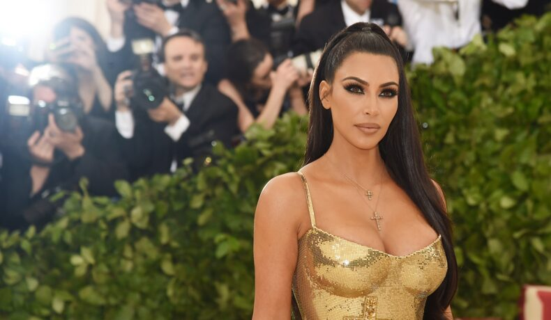 Kim Kardashian pe covorul roșu în timp ce poartă un top auriu și părul prins într-o coadă de ponei la o gală susținută la Muzeul Metropolitan de Artă din New York din 2018