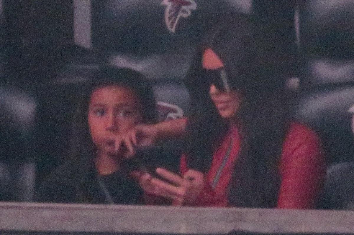 Kim Kardashian în timp ce stă pe scaun și se uită pe telefon alături de fetița ei