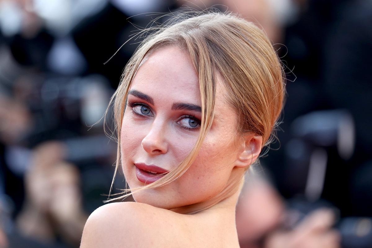 Portret al modelului Kimberley Garner care privește peste umăr la fotografi pe covorul roșu la festivalul de film de la Cannes din 2018