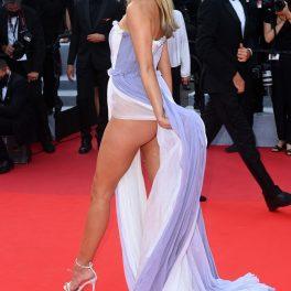 Kimberley Garner în timp ce pășește pe covorul roșu și își ține rochia cu mâna care îi lasă la vedere piciorul stâng