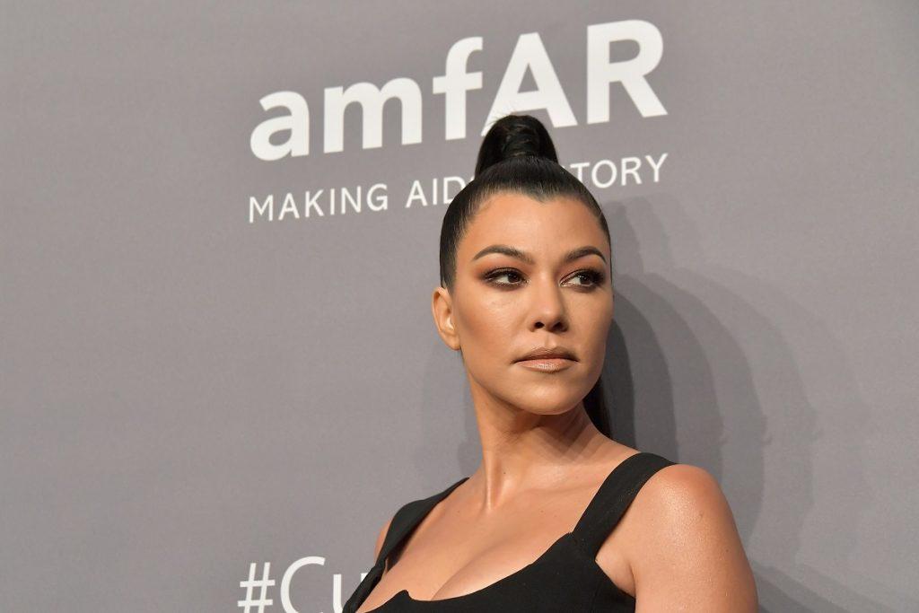 Kourtney Kardashian pe covorul roșu cu părul prins într-un coc în vârful capului la Cipriani Wall Street în 2019