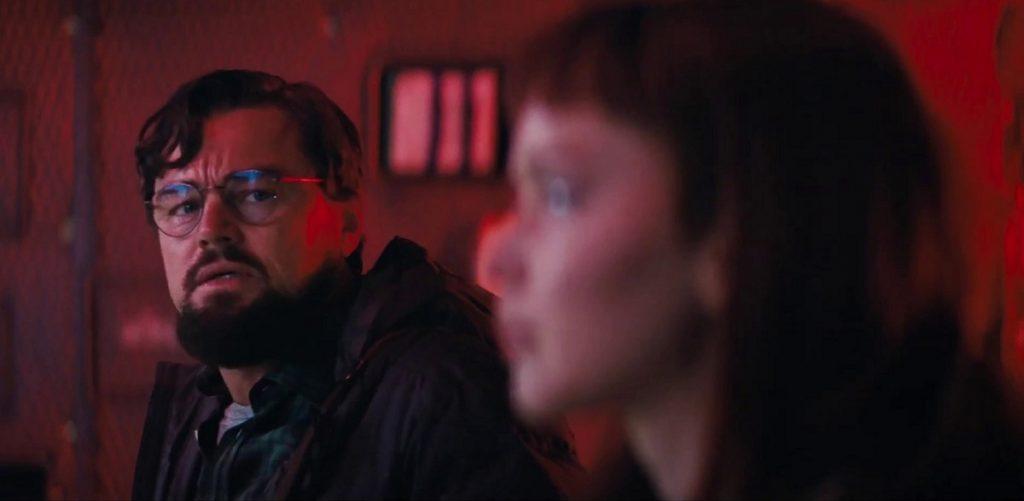 Leonardo DiCaprio alături de partenera sa de scenă într-o încăpere roșie în pelicula Don't Look Up