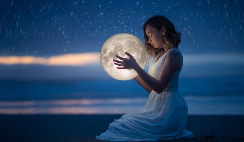 O femeie frumoasă care stă pe plajă în genunchi noaptea în timp ce ține în mâini Luna Plină intrată în zodia Vărsătorilor