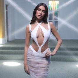 Madison Beer într-o rochie albă decupată pe trunchi în timp ce ține o mână în șold la MTV în Los Angeles în 2020