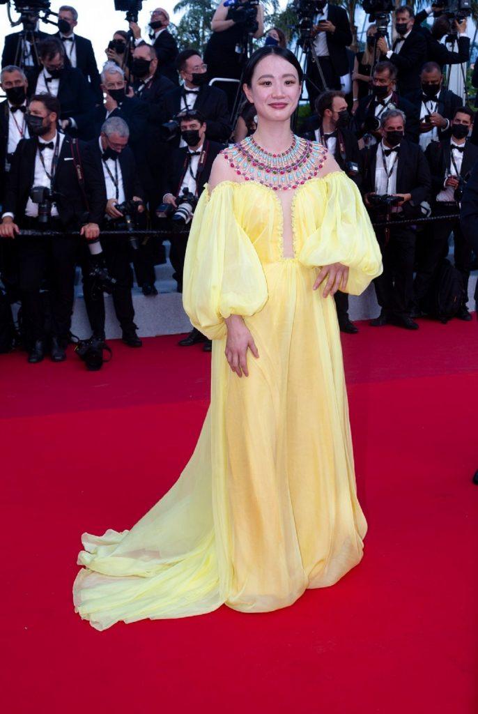 Actrița Meng Li în timp ce pozează pe covorul roșu unde poartă o rochie galbenă cu un colier inspirat din cultura indiană