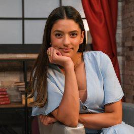 Actrița Oana Moșneagu în timp ce poartă o rochie albastră și stă sprijinită cu o mână sub bărbie la interviul pentru CaTine.Ro