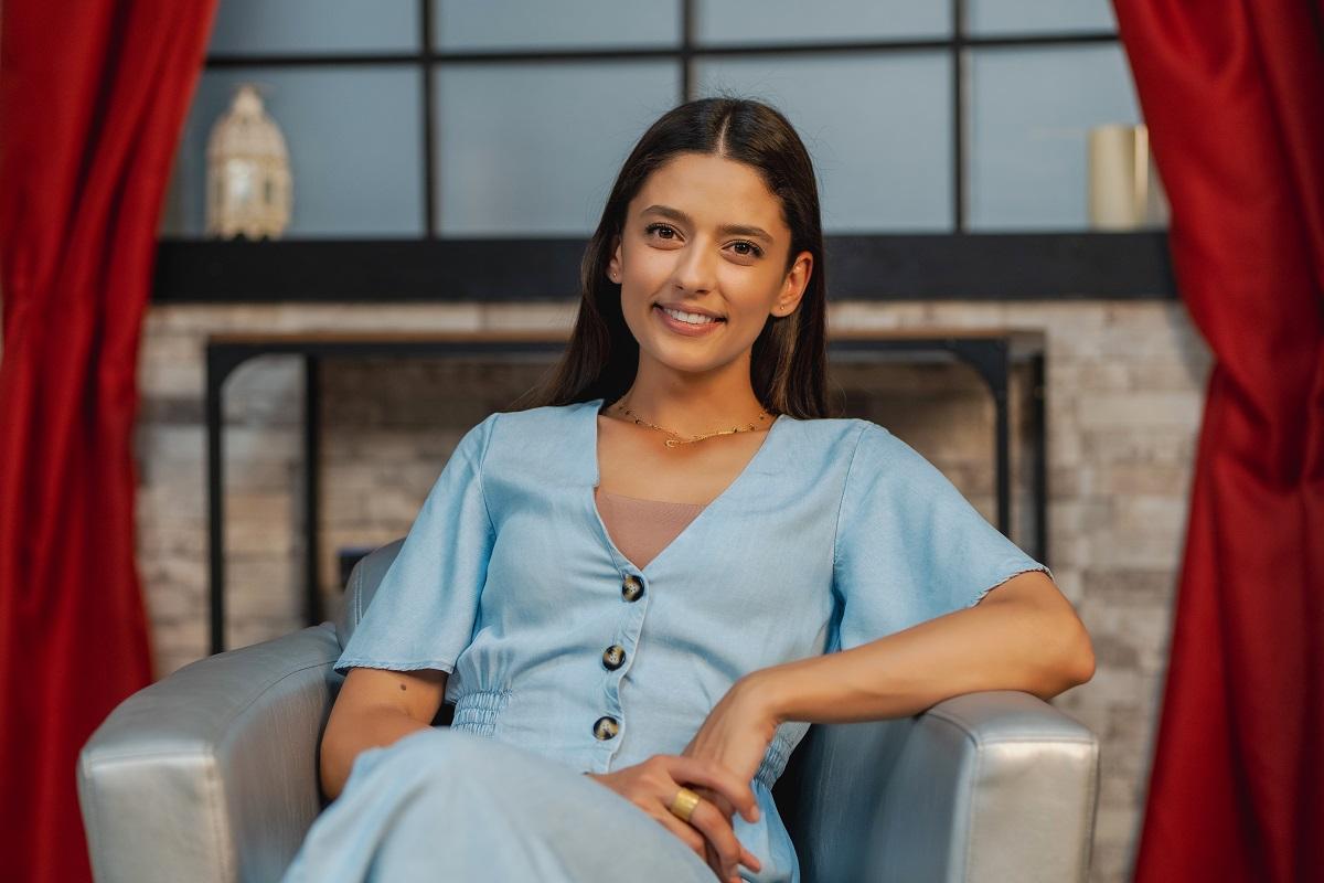 Actrița Oana Moșneagu într-un fotoliu argintiu în platourile de filmare pentru interviul CaTine.ro