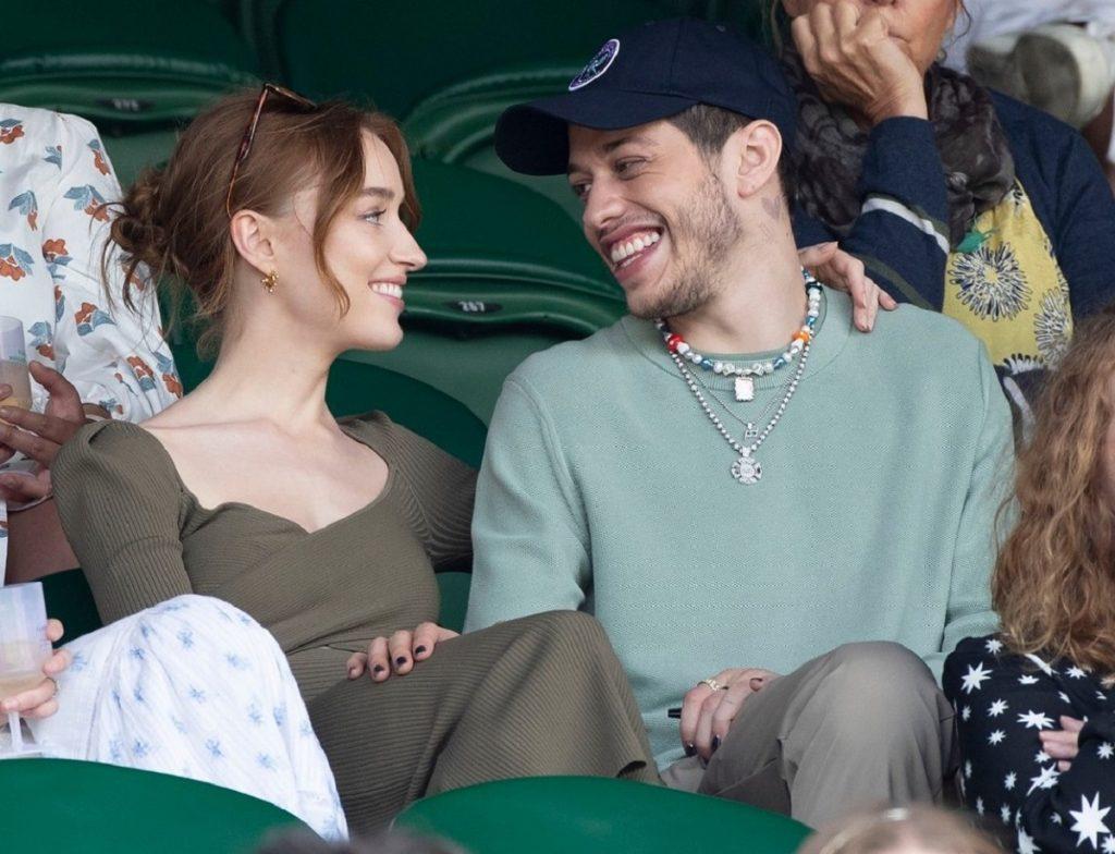 Phoebe Dynevor și Pete Davidson în timp ce se privesc unul pe celălalt și își zâmbesc în cadrul meciului de tenis de la turneul din Wimbledon