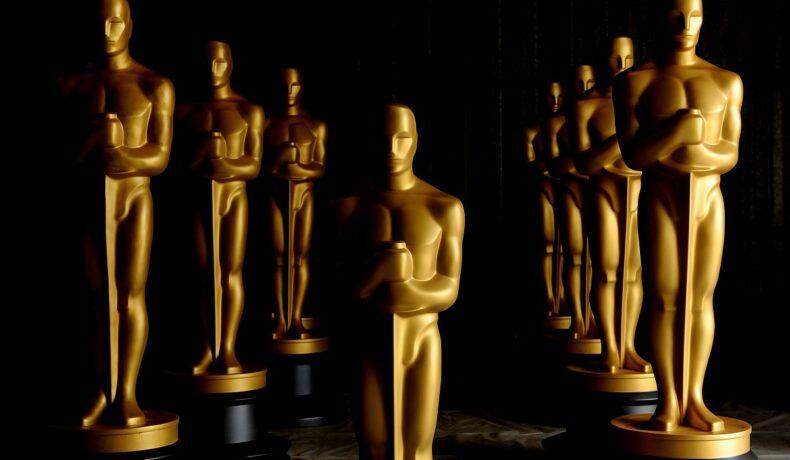 O încăpere neagră în care se află statui aurite în mărime naturală pentru decernarea premiilor după ce au fost anunțate predincțiile pentru Premiile Oscar 2022
