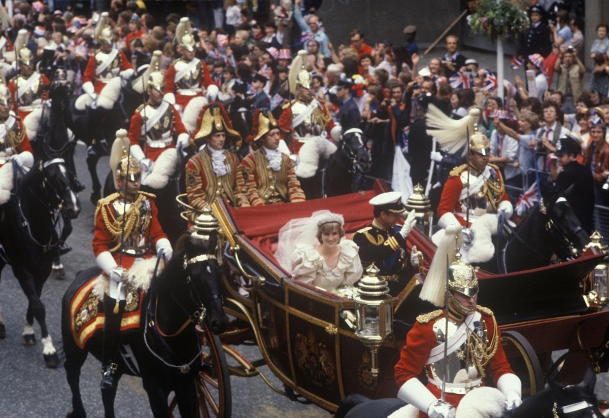 Lady Di în rochie de mireasă și Prințul Charles la costum in timp ce merg cu trasura dupa nunta regala din 1981