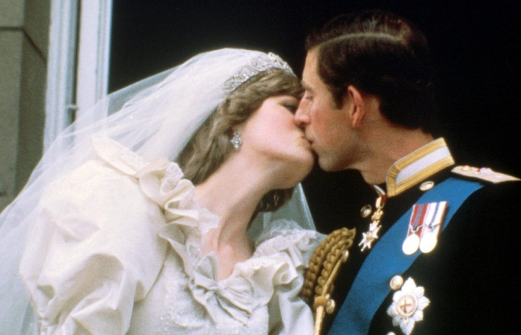 Prințesa Diana în rochie de mireasă în timp ce îl sărută pe Prințul Charles la balcon în 1981