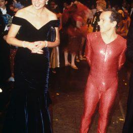 Porfesorul de dans al Prințesei Diana, Wayne Sleep, într-un costum cu paiete roșu alături de Lady Di îmbrăcată într-o rochie elegantă neagră în timp ce vorbesc la Carnavalul Păsărilor din cadrul Casei Regale de Operă în anul 1991