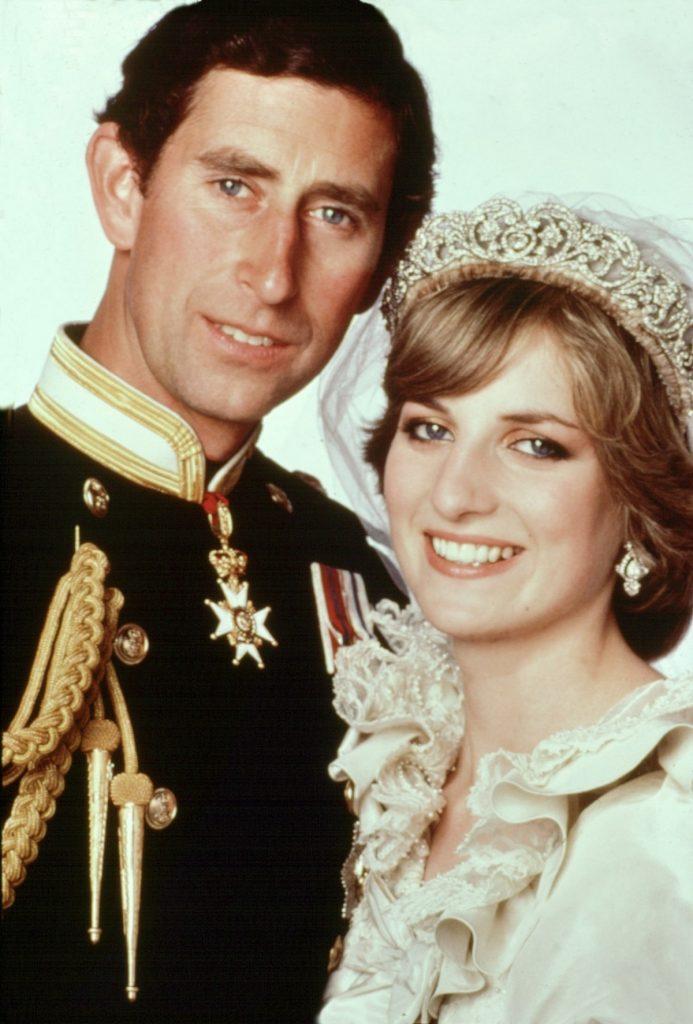 Portret cu Prințu Charles în uniformă militară care zâmbește, alături de soția sa, Prinșesa Diana care poartă rochie de mireasă la nunta lor din iulie 1981