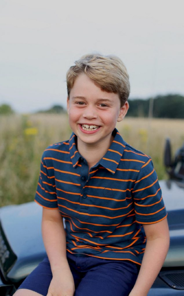 Portret al Prințului George care a împlinit 8 ani în timp ce stă pe capota unei mașini și zâmbește purtând un tricou albastru cu dungi orange și pantaloni scurți