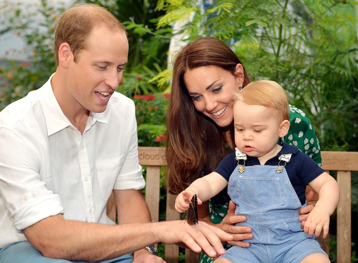 Prințul William alături de Ducesa Kate Middleton și Prințul George în timp ce micuțul privește un fluture de pe mâna tatălui său