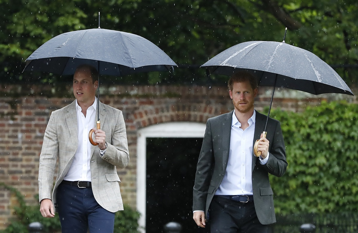 Prințul William purtând costum și ținând o umbrelă în mână este îngrijorat cu privire la careta fratelui său, Prințul Harry care stă lângă el cu umbrela în timp ce se îndreaptă către castelul Kensington