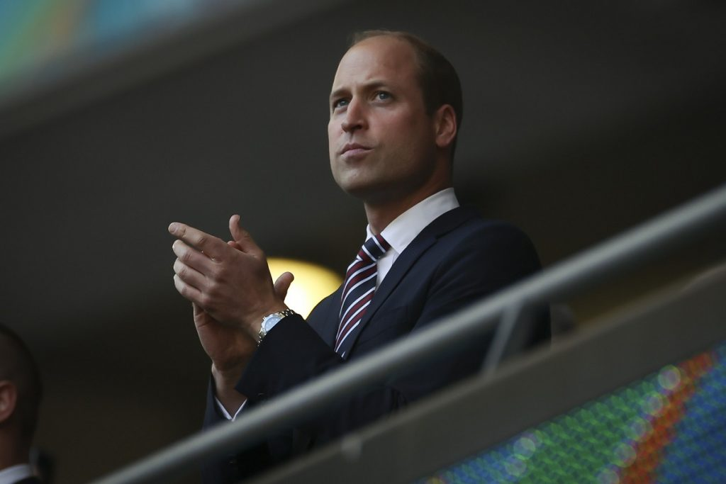 Prințul William la costum în timp ce aplaudă din tribuna unui stadion de fotbal la meciul Anglia-Danemarca din cadrul semifinalei Euro 2020