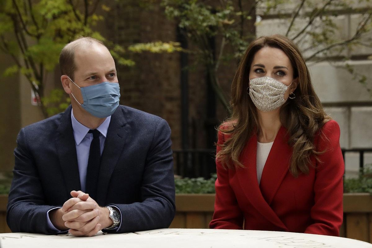 Prințul William îmbrăcat la costum și purtând mască, alături de Kate Middleton la sacou roșu care poartă la rândul său mască, a decis să nu se izoleze la Palatul Kensington alături de soția sa