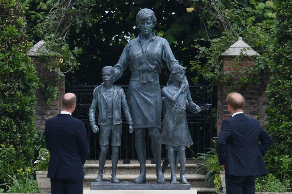 Prințul William și Prințul Harry în timp ce privesc statuia Prințesei Diana