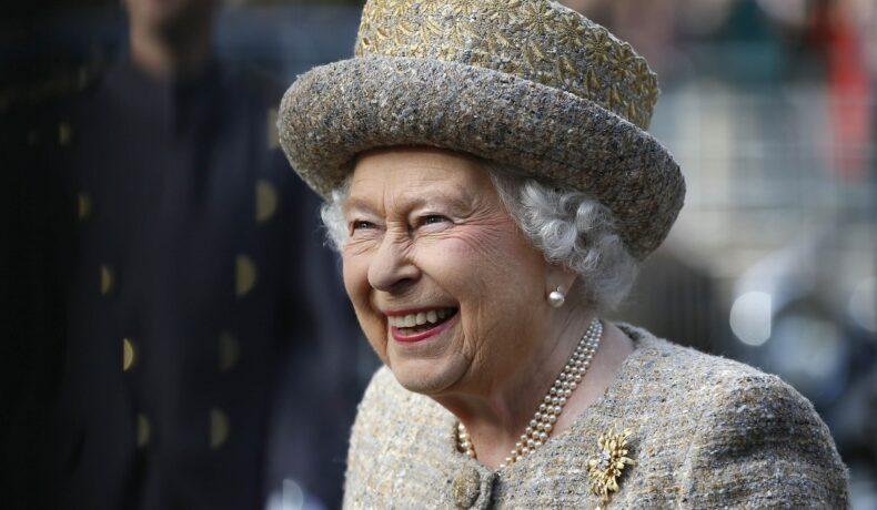 Regina Elisabeta îmbrăcată la costum argintiu cu pălărie în timp ce zâmbește la o întâlnire oficială din Londra în 2014, înainte să se afle că i-ar putea scoate pe Ducii de Sussex de pe lista invitaților la Jubileul de Platină
