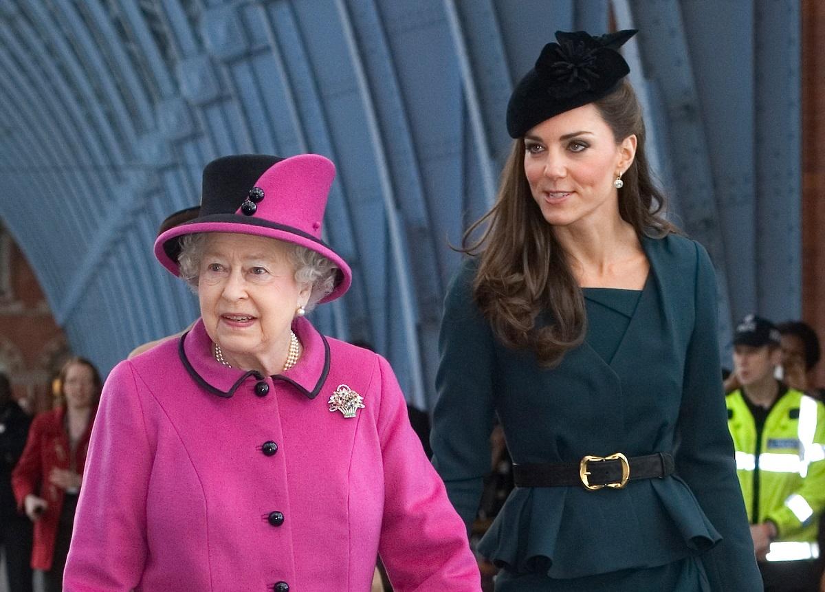 Regina Elisabeta într-un costum roz cu pălărie pe cap alături de Kate Middleton într-un costum verde smarland în timp ce aștaptă un tren pentru a vizita Leicester în 2012