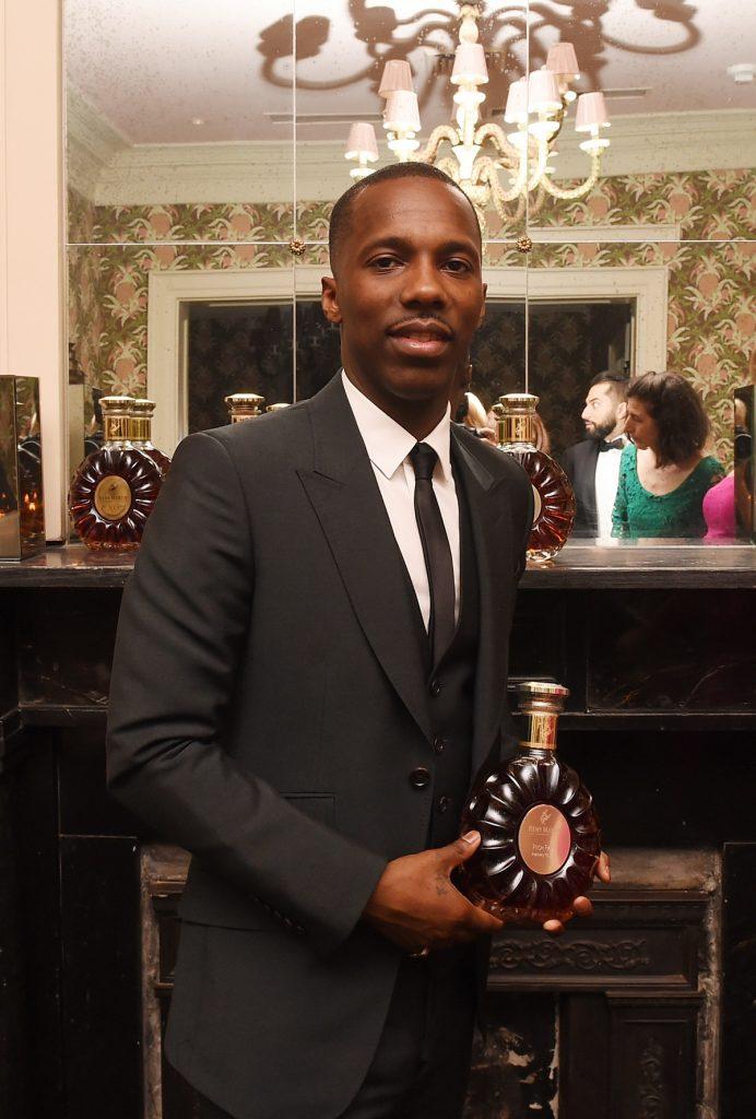 Agentul Sportiv Rich Paul îmbrăcat la costum în timp ce zâmbește și ține în mână o sticlă de băutură la un eveniment privat din New Orleans din anul 2017