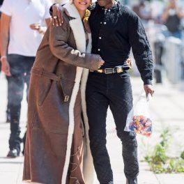 Artista Rihanna într-o ținută crem cu un batic pe cap în timp ce îl ține în brațe pe iubitul său A$AP Rocky la filmările celui mai recent proiect împreună