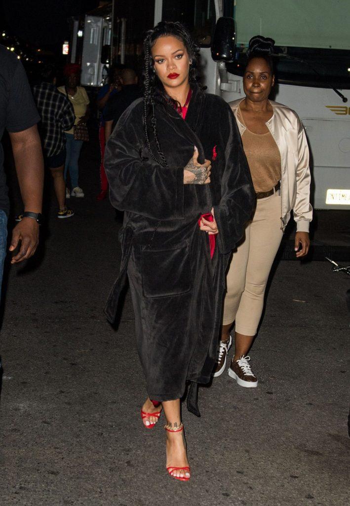 Apariția Rihannei într-un halat negru și tocuri roși în timp ce se află pe străzile din New York la filmarea noului său videoclip