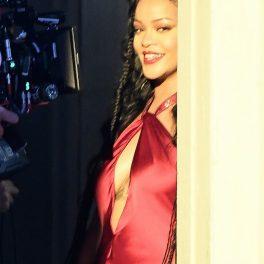 Rihanna în timp ce se sprijină de un perete într-o rochie roșie și este filmată pentru noul său videoclip muzical cu A$AP Rocky