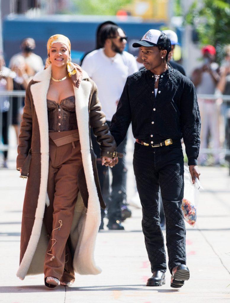 Rihanna într-o ținută monocromatică crem cu palton de iarnă și un batic galben pe cap în timp ce-l ține de mână pe iubitul său A$AP Rocky după ce au filmat împreună un nou proiect